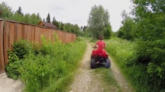 Woman rides on quad bike by country road at summer day. Stock Footage