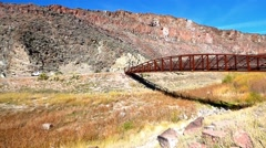 Rusty Metal Bridge Spanning a High Desert Canyon Stock Footage
