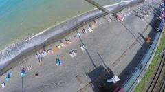 People get rest on sea beach near railway at summer Stock Footage