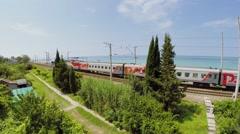 Train of RZD company rides near sea beach at summer Stock Footage