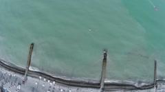 People swim in sea near pebble beach with sunbeds Stock Footage