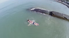 Retiree couple swim in sea with inflatable mattress near beach - stock footage