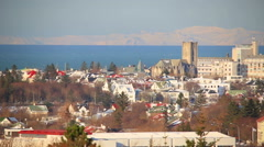 Reykjavik, Iceland downtown sunny winter day snowy mountains ocean pan Stock Footage