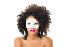 Young woman with short curly dark hair wearing a mask Stock Photos