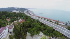 Coastal town with road traffic on sea shore at summer day. Stock Footage