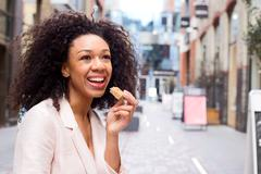 young woman enjoying a healthy snack in the street - stock photo