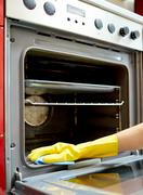 close up of woman cleaning oven at home kitchen - stock photo