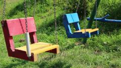 Colourful swings on children playground Stock Footage