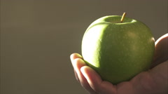 A Hand Holds a Green Apple - stock footage
