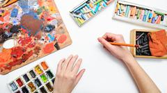 Artist's hand at work, paints, brushes and pencils - stock photo