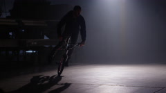 BMX rider doing tricks in dark warehouse. Stock Footage