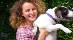 Beautiful Young Happy Woman Dancing with a Cute Dog Outdoors Stock Footage