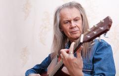 Middle-aged man playing guitar closeup Stock Photos