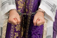 abuse in the church. priest with handcuffs - stock photo