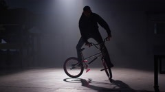 BMX rider doing tricks in dark warehouse. - stock footage