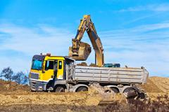 excavators at work at construction site - stock photo