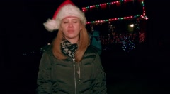 A young blonde woman waits outside of a house decorated for Christmas in the col - stock footage