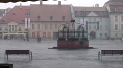 Heavy rain, people with umbrella, storm, wind, central square, medieval town Stock Footage