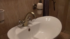 Faulty tap, water dripping, waste water, vintage, bathroom sink Stock Footage