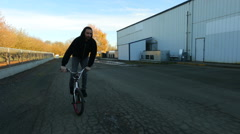 BMX rider going by warehouse. - stock footage