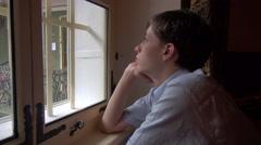 Depressed teenage boy, dreamy young man looking through window Stock Footage