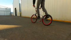 BMX rider doing tricks in warehouse. - stock footage