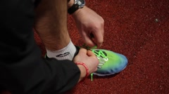 Athlete tying running shoe laces on athletics track Stock Footage