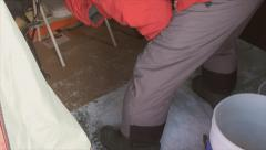 Man prepares, drill ice fishing holes inside tent Stock Footage