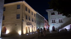 Tourists walking a medieval town's streets at night after dark in Transylvania Stock Footage