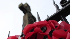 poppy wreath at a monument with railings and a focus shift to show cenotaph - stock footage