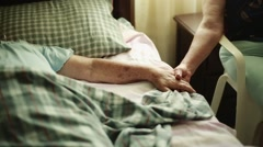 Elderly Woman lying down and holding another woman's hands Stock Footage