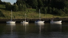 Line of 4 boats on a still uk river on a sunny summer day Stock Footage