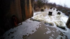 Water stream flowing out the underground tunnel into the river Stock Footage