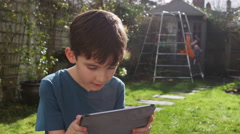Portrait of a young boy playing on his touchscreen tablet in a garden on a brigh Stock Footage