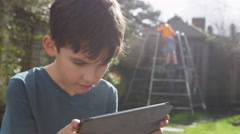 Young boy playing on his touchscreen tablet in the garden on a bright sunny day Stock Footage