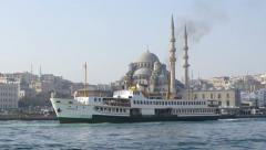 Ferryboat passing in front of Valide Sultan Mosque Stock Footage