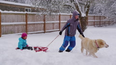 Kids pulling sled in snow - stock footage