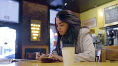 Mixed Race Teen Writes And Draws In Her Journal At A Coffee Shop (Dolly Shot) - stock footage