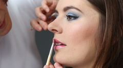 Makeup artist applying lip gloss to model lips, full HD Stock Footage