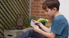 Young boy playing on his touchscreen tablet in the garden on a bright sunny day - stock footage