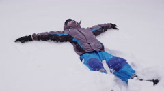 Boy making snow angel Stock Footage