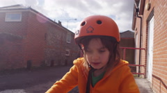 Little girl rides a cycle on a bright summers day Stock Footage