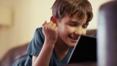 A very happy young boy playing on his tablet while lying down on couch at home. - stock footage