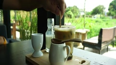 Stirring ice coffee with nature background Stock Footage