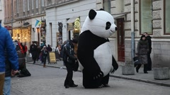 Large panda bear entertaining children and pedestrians downtown Lviv - stock footage