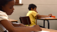 Schoolchild writing in notepad at school - stock footage