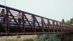 Group Of Friends Run On Bridge, Excited To Jump Off And Swim (Slow Motion) - stock footage