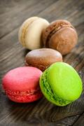 Different kinds of macaroons in stack on wooden background, selective focus - stock photo