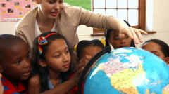 Teacher looking at globe with pupils - stock footage