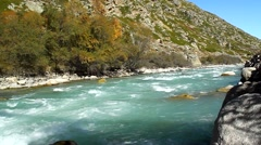 Blue River flows into the sunlit valley, autumn - stock footage